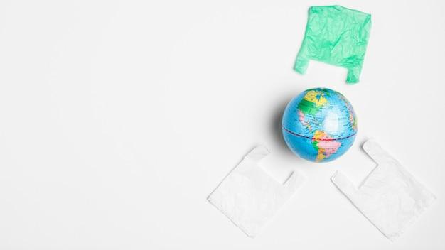 ビニール袋とコピースペースの地球の手袋のトップビュー