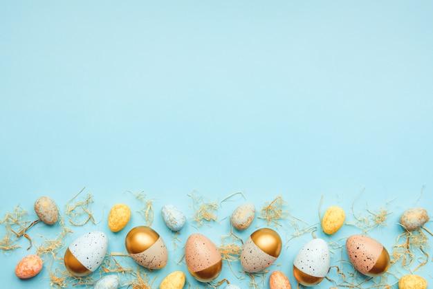 Вид сверху пасхальных яиц, окрашенных золотой краской и разными цветами. синий фон. скопируйте пространство.