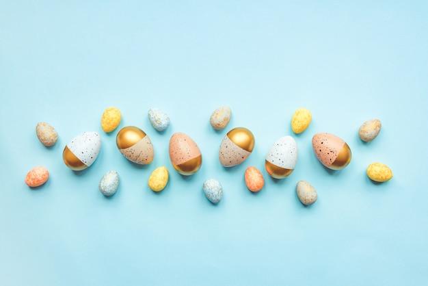 Вид сверху на пасхальные яйца, окрашенные золотой краской и разными цветами