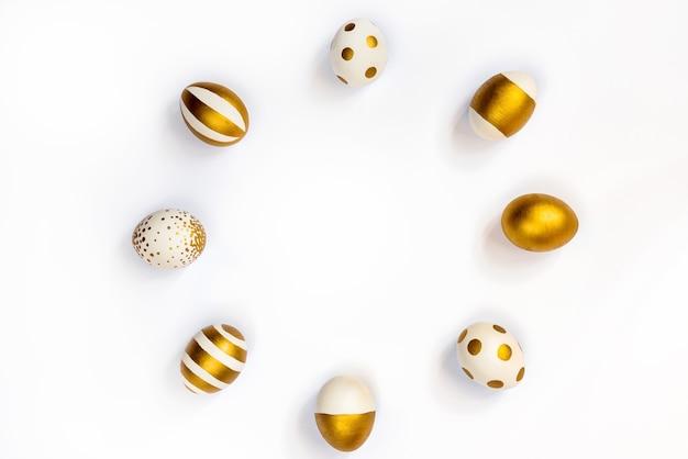 円形に配置された金色のペンキで着色されたイースターエッグの上面図。白色の背景。スペースをコピーします。