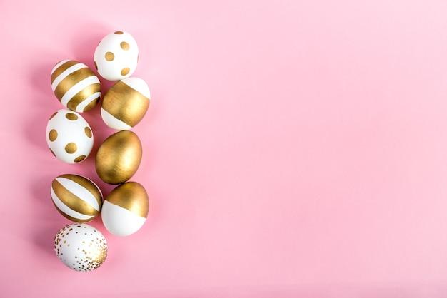 Вид сверху пасхальных яиц, окрашенных золотой краской. розовый фон.