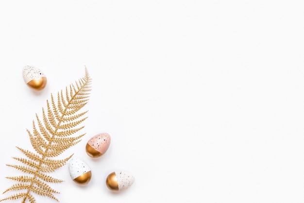 Вид сверху пасхальных яиц, окрашенных золотой краской. разнообразный красивый дизайн. белый фон.