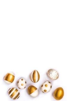 Вид сверху пасхальных яиц, окрашенных золотой краской. белый фон.