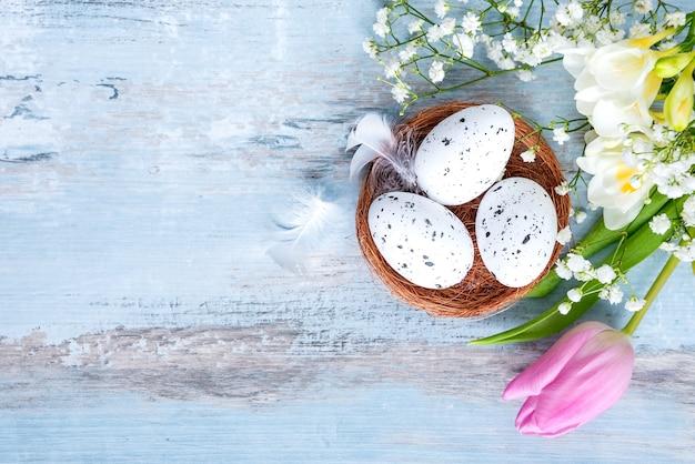 Вид сверху пасхальных яиц в гнезде. весенние цветы и перья над голубым деревенским деревянным столом.