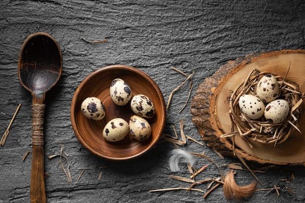 Вид сверху пасхальных яиц в птичьем гнезде и тарелке с деревянной ложкой