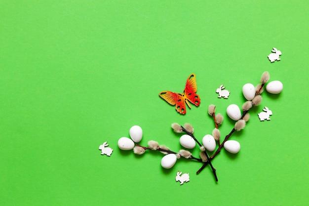 イースターエッグ、ネコヤナギ、小さなウサギの置物と羽の上面図。イースターのコンセプト
