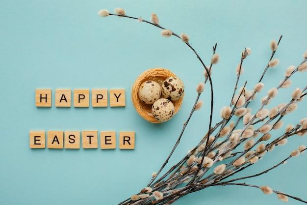Вид сверху пасхальных яиц с приветствием и ветками