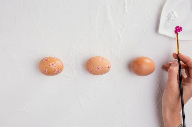 Вид сверху пасхальных яиц с кистью в руке