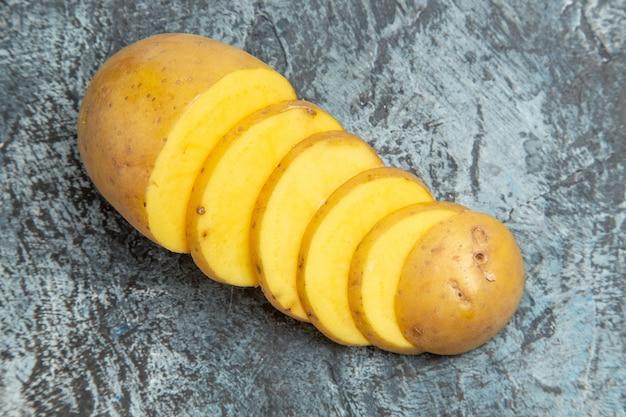 灰色の背景の簡単でおいしい皮をむいていないジャガイモのスライスの上面図