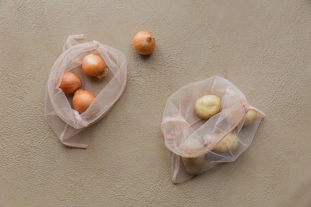 Вид сверху на эко-мешок на кулиске с луком и картошкой. покупка без вреда для природы в антипластиковых пакетах без отходов.