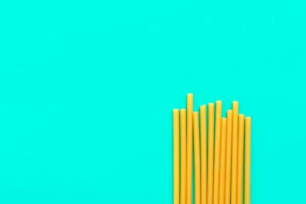 Вид сверху на эко-соломинки для макарон на зеленом фоне с копией пространства новая тенденция биоразлагаемых соломок с ...