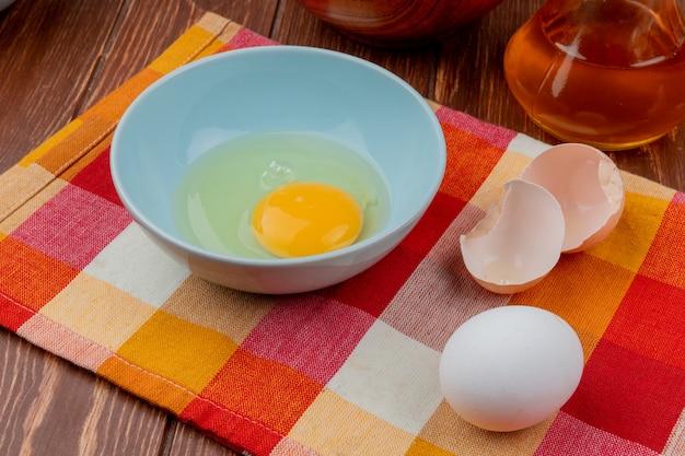 木製の背景に酢とチェックのテーブルクロスの上の青いボウルに卵黄と白のトップビュー