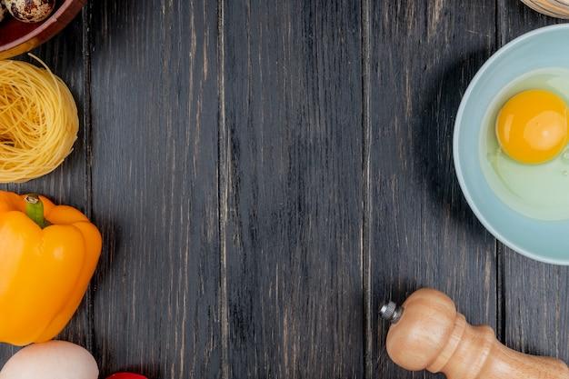 コピースペースを持つ木製の背景にオレンジ色のピーマンとボウルに卵黄と白のトップビュー