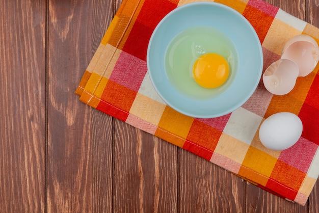 コピースペースを持つ木製の背景にチェックされた布の上のひびの入った卵の殻と白いボウルに卵黄と白の平面図