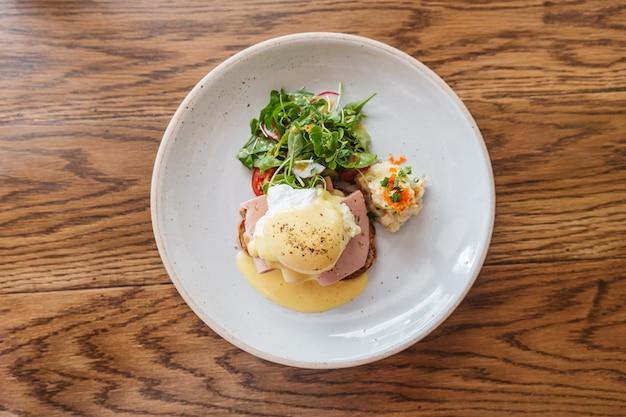 Вид сверху яйца бенедикт с ветчиной, тостами и картофельным пюре. подается с салатом в белой тарелке на деревянный стол.