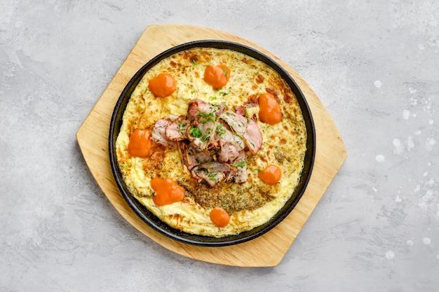 Вид сверху на яйца с беконом и помидорами, запеченные в духовке на чугунной сковороде
