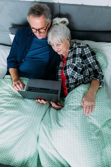 Top view of elderly couple in bed with laptop