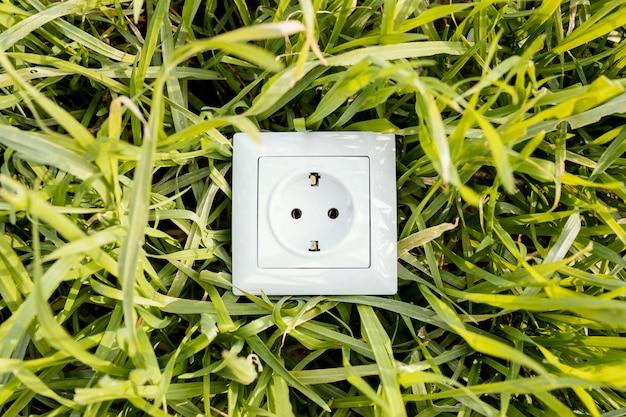 Вид сверху электрической розетки на зеленой траве