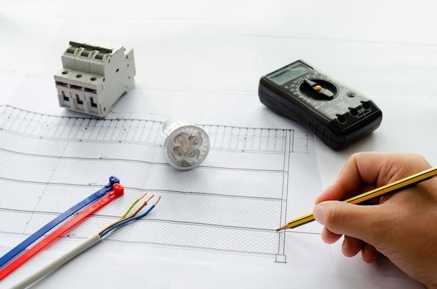 Вид сверху электрических инструментов и материалов для электрической системы, кабелей и кабельных стяжек, выключателей, светодиодной лампы и вольтметра на пустое пространство