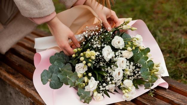 야외 꽃의 꽃다발을 고정하는 우아한 여자의 상위 뷰