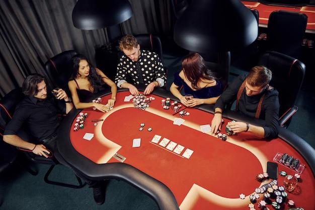 Вид сверху элегантных молодых людей, играющих в покер в казино
