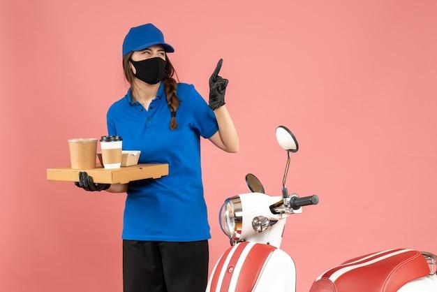 パステル ピーチ色の背景に上向きのコーヒーの小さなケーキを保持しているオートバイの隣に立っている医療マスク手袋を着た感情的な宅配便の女の子のトップ ビュー