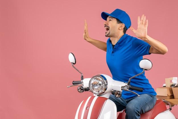 パステル調の桃の背景に10を示す注文を配達するスクーターに座っている帽子をかぶった感情的な宅配業者のトップビュー