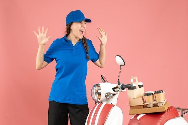 파스텔 복숭아 색 배경에 그것에 커피와 작은 케이크와 함께 motocycle 옆에 서있는 감정적 인 택배 아가씨의 상위 뷰