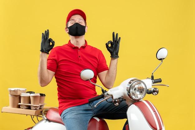 何かを夢見てスクーターに座って注文を配信医療マスクで赤いブラウスと帽子の手袋を身に着けている感情的な若い大人の上面図