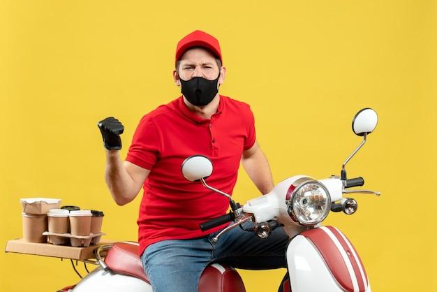 다시 가리키는 스쿠터에 앉아 주문을 제공하는 의료 마스크에 빨간 블라우스와 모자 장갑을 착용하는 감정적 인 젊은 성인의 상위 뷰