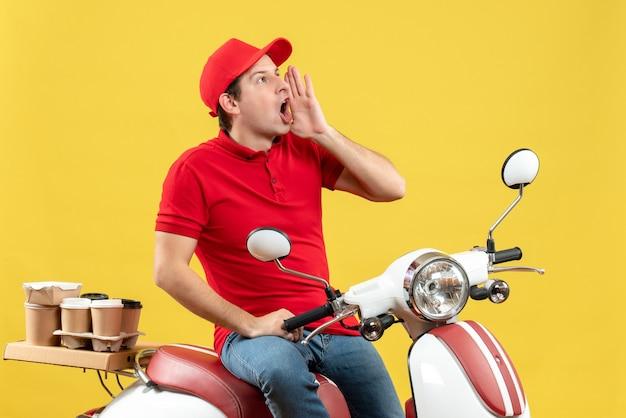 赤いブラウスと帽子をかぶって、黄色の背景で誰かを呼び出す注文を配信する感情的な若い男の上面図