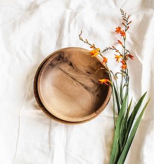 空の茶色の丸い手作りの木製ボウルと白い綿のテーブルクロスにオレンジ色の花の上面図。フラットレイ。コピーsapce