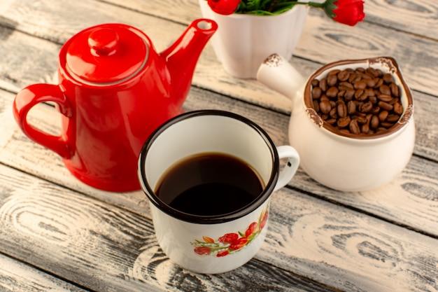木製の机の上の赤いやかん茶色コーヒーの種子と花と空のカップのトップビュー