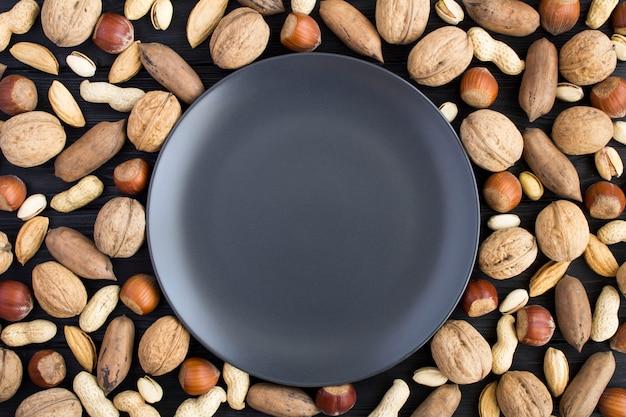 空の暗いプレートとさまざまなナッツのトップビュー