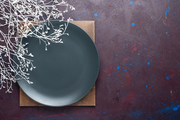 暗い表面に形成された丸い空の暗いプレートの上面図