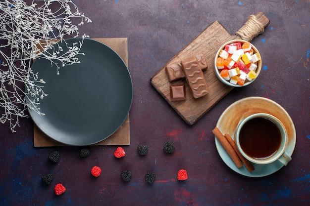 Вид сверху пустой темной круглой тарелки с чаем и конфетами на темной поверхности