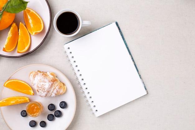 Вид сверху на пустой дневник и чашку кофе, круассан, чернику и сочные апельсины