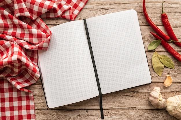 Вид сверху пустой меню книги со скатертью и перцем чили