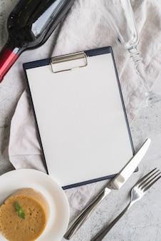Вид сверху пустого меню с бутылкой вина и столовыми приборами