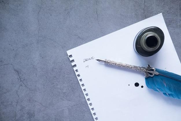 Вид сверху пустой бумаги, перьевой ручки и чернил на черном фоне