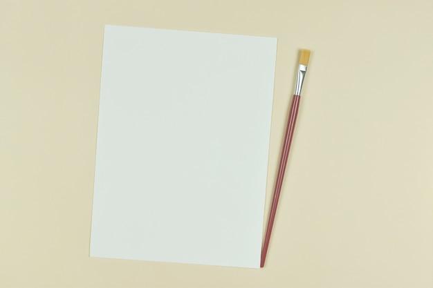 側面に絵筆とコピースペースであなたの作品をデザインする空の紙シートの上面図