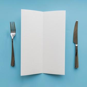 Вид сверху пустой бумаги с вилкой и ножом