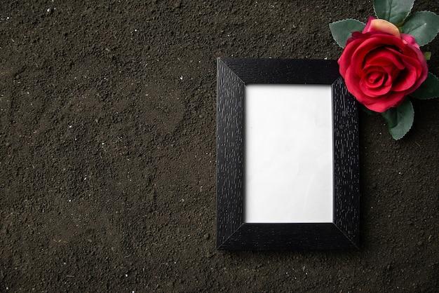Вид сверху пустой фоторамки с красным цветком на темной почве