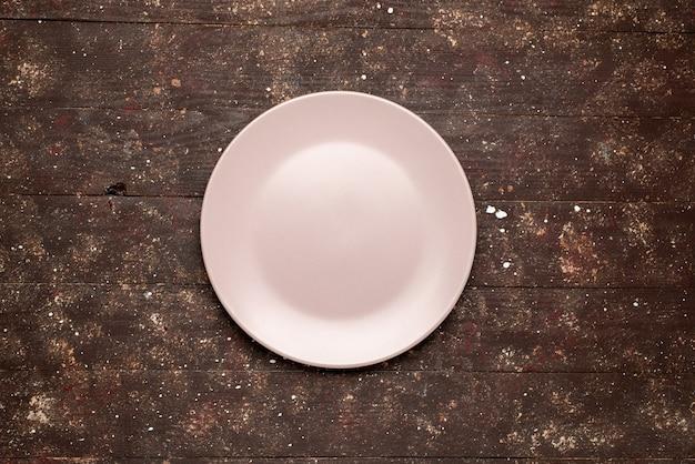 Вид сверху пустой розовой тарелки, изолированной на коричневой деревенской, деревянной деревянной тарелке