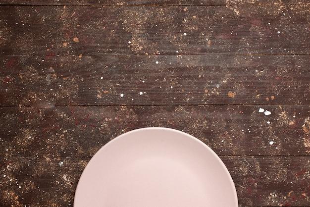 茶色の素朴なプレートウッドにピンク色の空のプレートの上面図