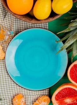 布と緑の背景にタンジェリングレープフルーツレモンの周りの柑橘系の果物と空のプレートのトップビュー