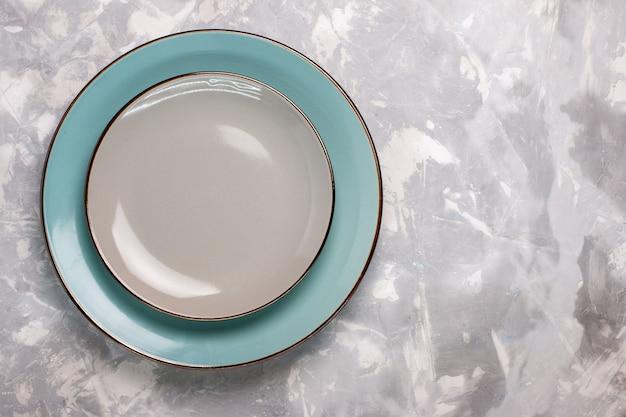 白い机の上のガラスで作られた空のプレートの上面図