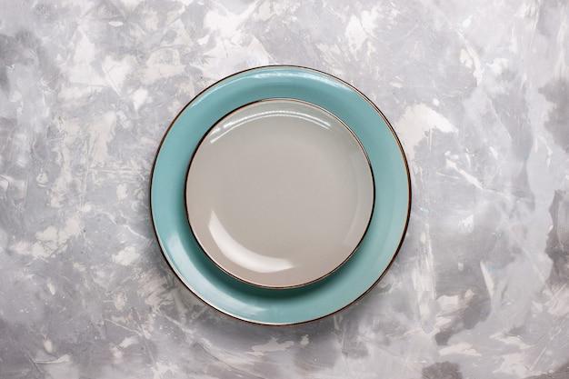 白い表面にガラスで作られた空のプレートの上面図