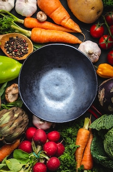 素朴な黒いコンクリートの背景に空の素朴なセラミックボウルと新鮮な農場の有機野菜の上面図。秋の収穫、ベジタリアン料理、またはテキスト用のスペースを備えた清潔で健康的な食事のコンセプト