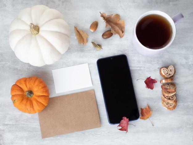 空の白いカード、ビンテージ紙、スマートフォン、テーブルの上にカボチャと紅葉の上面図